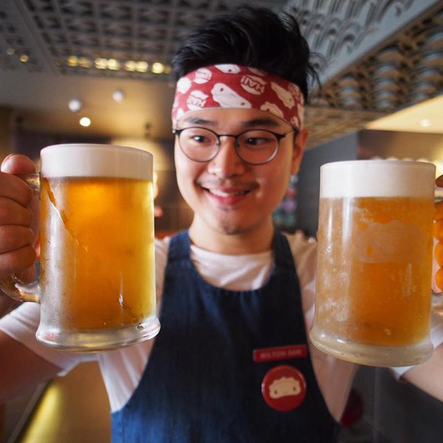 Staff member with a Japanese beer in each hand smiling.