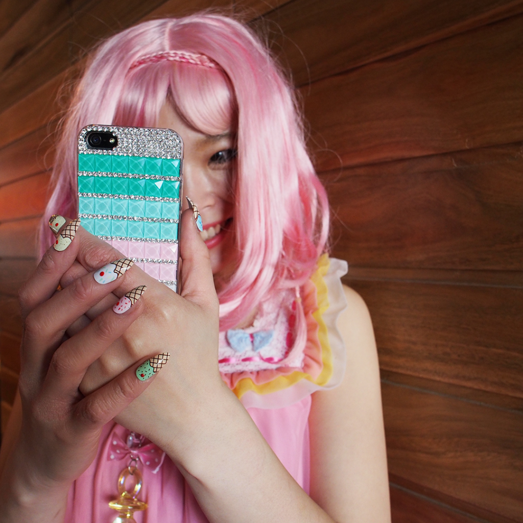 Harajuku girl holding up a cute phone for the Instagram competition
