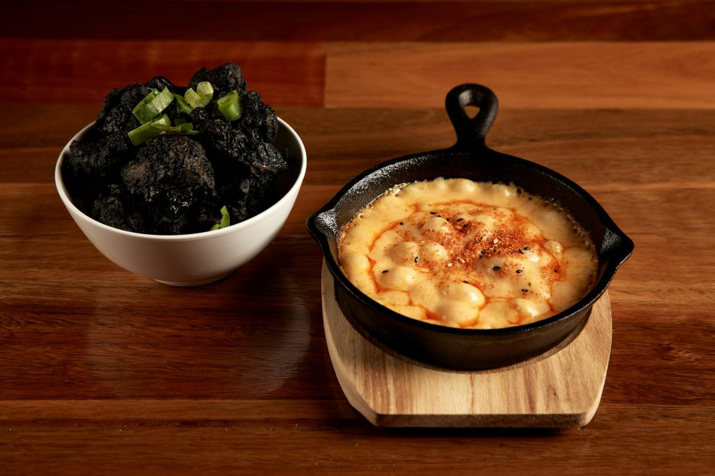 Bowl of Charcoal Karaage Chicken with a Cast iron pot of bubbling cheese