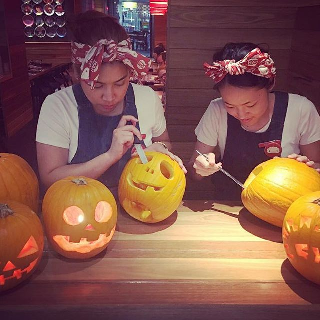 Two girls carving pumpkins for halloween